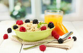 Tasty oatmeal with berries and glass of juice on table, on window background — Stock Photo