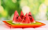 Sladký meloun plátky na desky na dřevěný stůl na přírodní pozadí — Stock fotografie