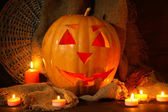 Halloween pumpkin and candles, on wooden background — Stock Photo