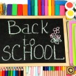 The words 'Back to School' written in chalk on the small school desk with various school supplies close-up — Stock Photo #14574873