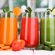 Fresh vegetable juices on wooden table, on window background — Stock Photo #14576225