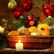Christmas composition in basket with oranges and fir tree, on wooden background — Foto de Stock