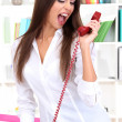 Angry businesswoman with phone at office - Stock Photo