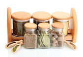 Jars and wooden spoons on shelf with spices isolated on white — Stock Photo