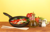 Frying pan with vegetables on yellow background — Stock Photo