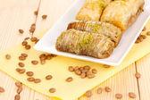 Sweet baklava on plate on wooden background — Stock Photo