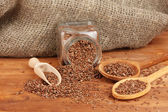 Flax seeds in wooden spoons on wooden background close-up — Stock Photo