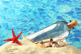 Glass bottle with note inside on sand, on blue sea background — Stock Photo