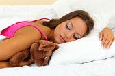 Jonge mooie vrouw slapen met pluizig beer in bed — Stockfoto