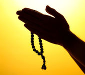 Male hands with rosary, on yellow background — Stock Photo