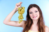 Beautiful woman with grape on blue background — Stock Photo