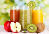 Fresh fruit juices on wooden table, on green background — Stock Photo