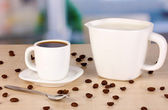 A cup of strong coffee and sweet cream on wooden table on room background — Stock Photo