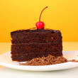 Chocolate sacher cake on yellow background - Stock Photo