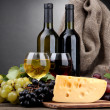 Bottles and glasses of wine, cheese and grapes on grey background — Stock Photo #14615857