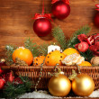 Christmas composition in basket with oranges and fir tree, on wooden background - Stockfoto