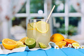 Citrus lemonade in glass bank of citrus around on blue wooden table on window background — Stock Photo