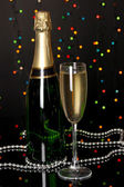 Celebratory champagne with wineglass on Christmas lights background — Stock Photo