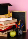 Książki i magister wpr z kuratorium na drewnianym stole na różowym tle — Zdjęcie stockowe