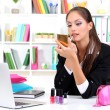 Stock Photo: Young business womlooking in mirror and using lipstick at her worlplace