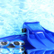 Blue flippers and goggles on blue sea background — ストック写真