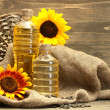 Stock Photo: Oil in bottles, sunflowers and seeds, on wooden background