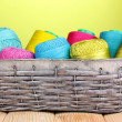 Bright threads in basket on wooden table on green background - Lizenzfreies Foto