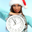 Beautiful young woman with clock, on blue background — Stock Photo