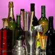 Collection of drinks, cocktail shaker and other bartender equipment on color background — Stock Photo