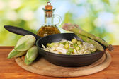 Pan with coleslaw, asparagus and chicory on wooden table on natural background — Stock Photo