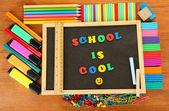 Pequeña pizarra con escuela suministra sobre fondo de madera. regreso a la escuela — Foto de Stock