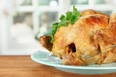 Roasted whole chicken on a blue plate on wooden background close-up — Stock Photo