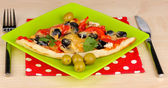 Výborné řezy pizzy na barevné desky close-up na dřevěný stůl — Stock fotografie