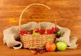 Cultivo de bayas y frutas en una cesta en primer plano de fondo de madera — Foto de Stock