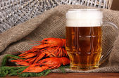 Tasty boiled crayfishes and beer on table on sackcloth background — Stock Photo