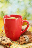 Cup of hot tea and autumn leaves, on rain background — Stock Photo
