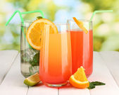 Three cocktails on wooden table on bright background — Stock Photo
