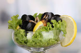 Snack of mussels and lemon on vase on room background close-up — Stock Photo