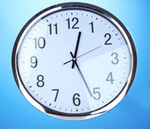 Round office clock on blue background — Stock Photo