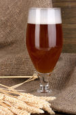 Glass of beer on wooden table on sacking background — Stock Photo
