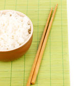 Bowl of rice and chopsticks on bamboo mat isolated on white — Stock Photo