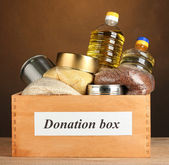 Donation box with food on brown background close-up — Stock Photo