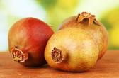 Unripe pomegranates on green background close-up — Stock Photo