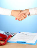 Shaking hands after signing the agreement, on a blue background — Stock Photo