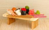 Sushi delicioso servido na tábua de madeira na esteira de bambu — Foto Stock