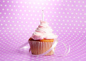 Tasty birthday cupcake with candle, on violet background — Stock Photo