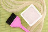 Hair dye in bowl and brush for hair coloring on green bamboo mat, close-up — 图库照片