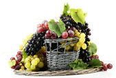 Assortment of ripe sweet grapes in basket, isolated on white — Photo