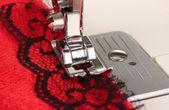 Närbild av symaskin verksam del med rött tyg — Stockfoto