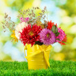 Bright yellow bucket with flowers on green background — Stock Photo